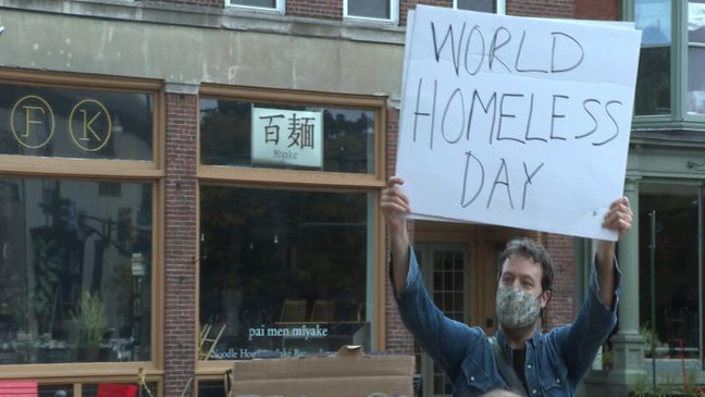 """A homeless advocate holds a """"World Homeless Day"""" sign at Longfellow Square. (WGME)"""